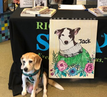 Sadie sits beside a drawing of Jack at our signing table.